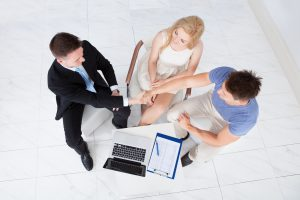 Young Couple Shaking Hands With Financial Consultant